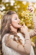 Young woman eating grapes outdoor. Sensual blonde female smiling