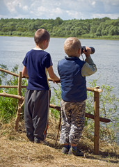 The boys see in the binoculars on the river