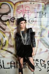 Punk woman standing at wall