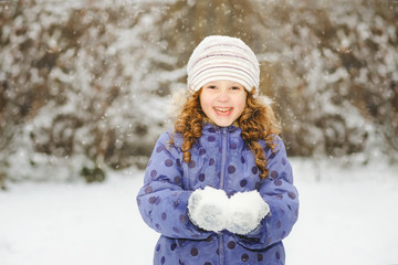 Winter portrait of a little smiling girl, holds in its hands sno