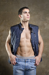 Sexy man posing shirtless with jacket