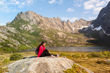Young tourist woman is sitting  on stone near mountain lake