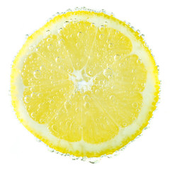 Fresh lemon in soda water covered with bubbles on white