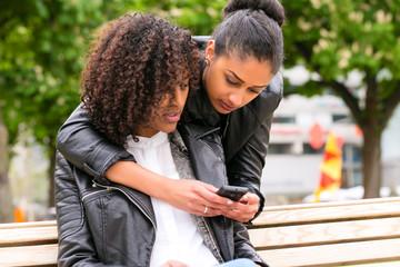 Beste Freunde chatten mit Smartphone auf Parkbank