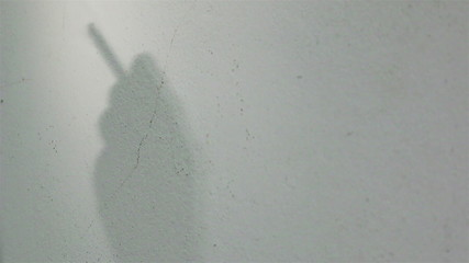 Shadow of man smoking a cigarette on the wall