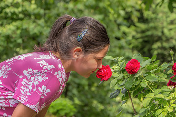 Cute little girl in the garden with a rose