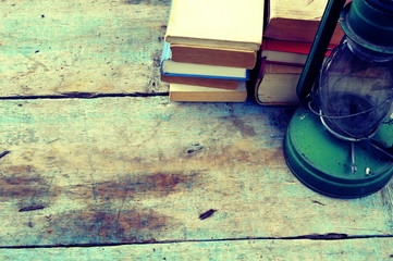 Old books with lantern on a wooden background