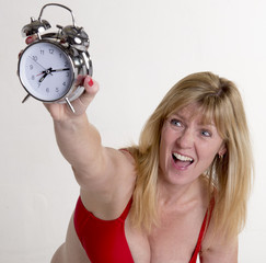 Angry woman holding alarm clock