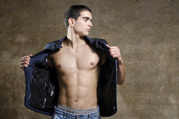 Sexy man posing shirtless with jacket