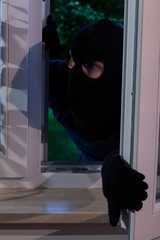 Burglar opening the window