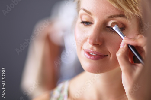 Artist doing professional make up of woman - 73219289