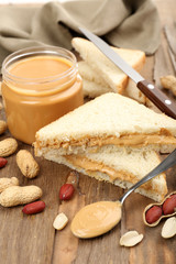 Bread slices with creamy peanut butter on wooden table