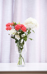 Beautiful flowers in vase on curtains background