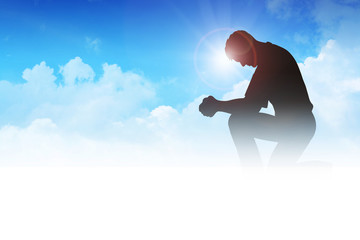 Silhouette illustration of a man praying among the clouds
