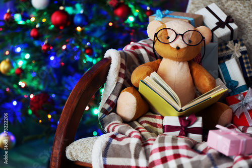 canvas print picture Teddy bear with book and gift boxes in rocking chair