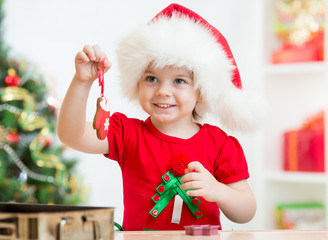 kid girl in Santa hat holding Christmas biscuits