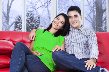 Casual couple sitting on red sofa