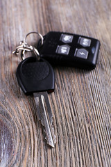 Car key with remote control on wooden table, close-up