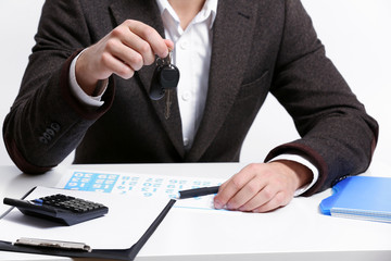 Businessman with car key in office
