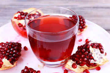 Ripe pomegranate and glass of juice on wooden table