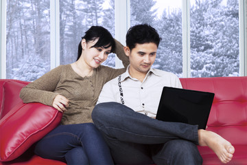 Couple sitting on couch using notebook