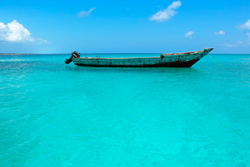 Wooden boat on the clear turquoise water of Zanzibar island