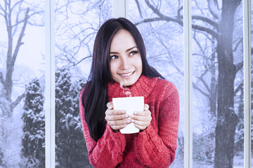 Girl wearing jumper enjoy hot drink