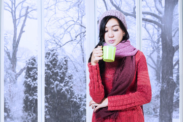 Girl wearing sweater and blow warm drink
