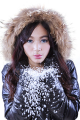 Girl with fur jacket blowing snow