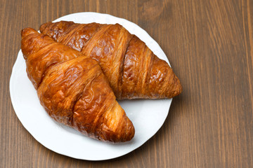 fresh croissants on a plate, top view