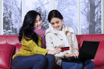 Girls in winter clothes shopping online