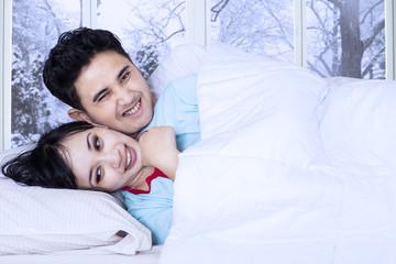 Happy couple jest on bed