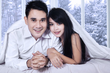 Happy couple under blanket in winter day