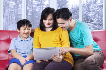 Hispanic family using tablet at home