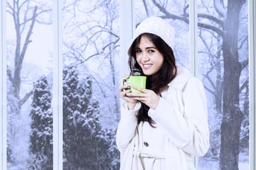 Lovely woman in winter coat drinks coffee