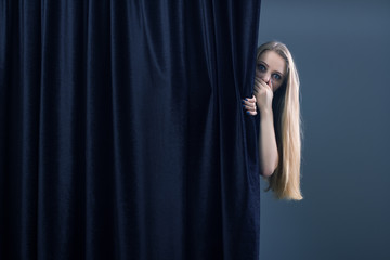 Frightened girl hiding behind a curtain.