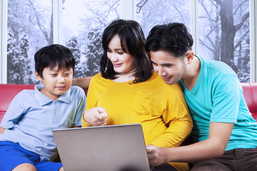 Parents showing laptop to their son