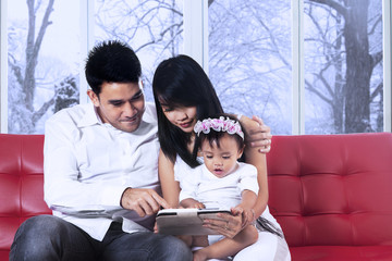 Parents using tablet with their daughter