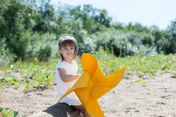 Smiling little girl playing with windmill