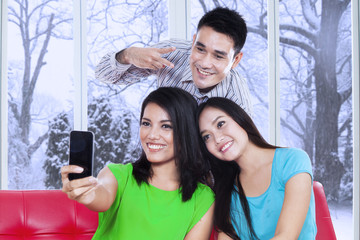 Three friends taking picture with cellphone