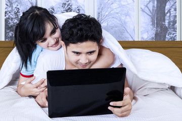 Woman embrace her husband while using laptop