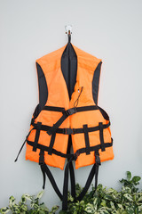 Orange Life jacket hung in wall