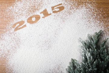 Inscription 2015 on flour and Christmas tree on a wooden table