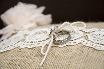 wedding rings on burlap pillow and lace