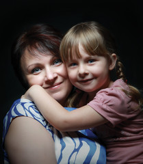 Mom and daughter cuddling with smiles