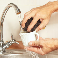 Hands with sponge wash cup under running water in kitchen