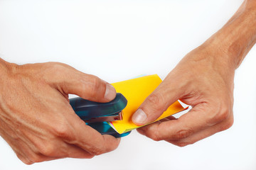 Hands fastened paper stapler on a white background
