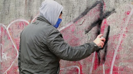 Man with color spray can near the old stone wall