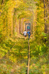 Couple walking towards the train at fall landscape tunnel