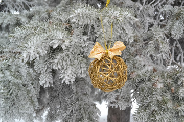 ball with bow-knot on the branch of snow christmas tree